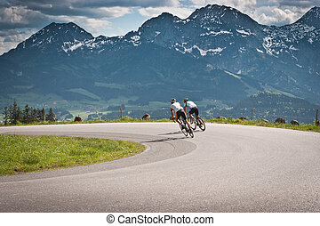 Two bikers on the road in mountains with Alps in background. Salzkammergut, Austria.