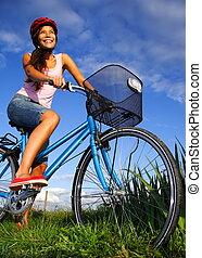 Biking woman - Woman biking under deep blue sky in the...