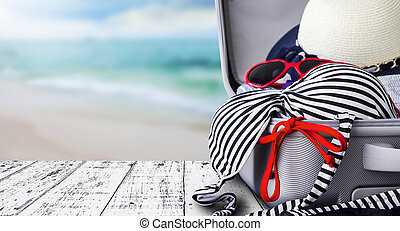 Bikini and clothes in luggage on white wooden