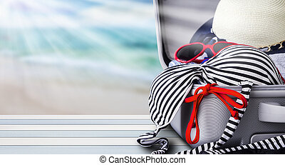 Bikini and clothes in luggage on wooden