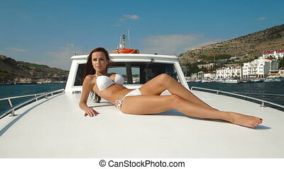 Attractive bikini woman sunbathing on luxury yacht