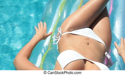 Young bikini woman sunbathing on air bed in pool