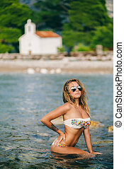 bikini girl model on beach in sea water