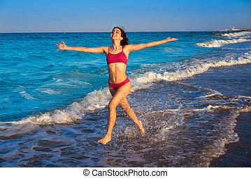 Bikini girl running to the beach shore water