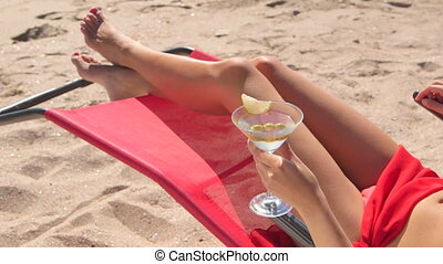 Bikini girl with cocktail relaxing on sandy summer beach