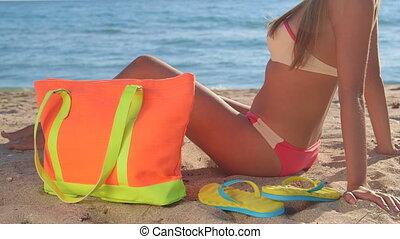 Bikini girl with colorful accessories on sandy beach