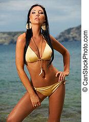 Bikini in action - Beautiful young Sexy woman posing in gold...