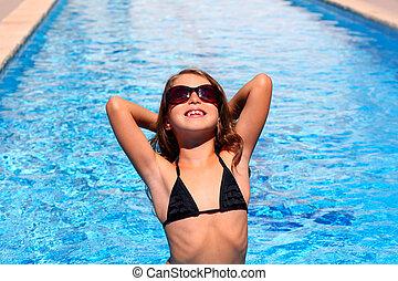 bikini kid girl with sunglasses in blue pool
