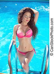 Bikini model. Beautiful sexy girl posing in blue swimming pool on the beach. Vacation. Tanned woman.