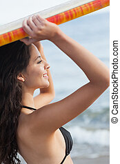Bikini woman holding surfboard over head at beach