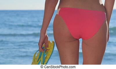 Bikini woman holding yellow flip-flops on the beach in front...