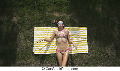 Bikini woman on towel over grass.