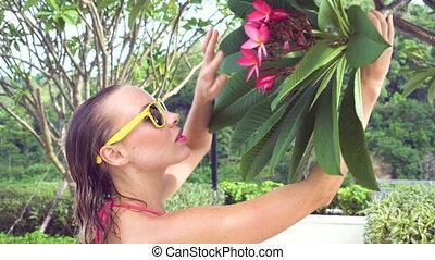 Bikini woman smelling flower.