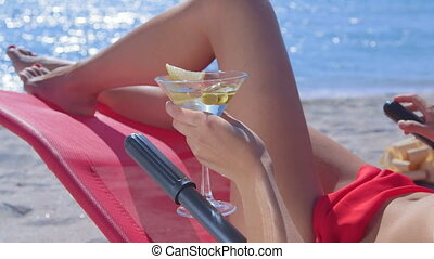 Bikini woman with cocktail glass relaxing on tropical beach close-up