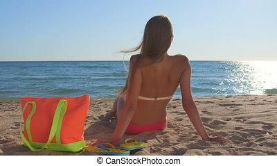 Bikini woman with colorful accessories enjoying summer beach vacation