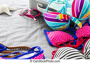 Bikinis and clothes in luggage on the bed