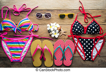 Bikinis, sunglasses, shoes, two sets placed on a wooden floor