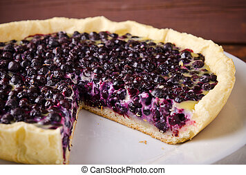 Bilberry, blueberry tart with lavender on white plate, wooden background