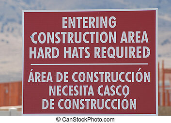 Bilingual Sign - Bilingual construction sign warning workers...