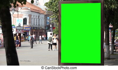 Billboard near a road in a city with a green screen.