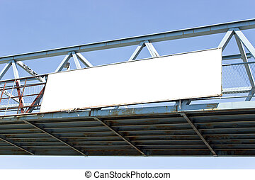 Billboard on pedestrian bridge over blue sky