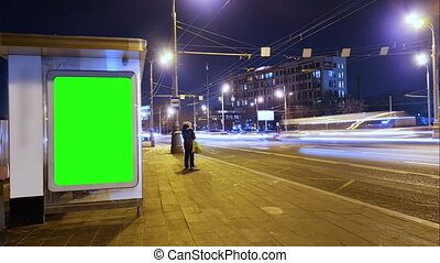 Billboard with a chroma key green screen on n bus stop at night. Time Lapse
