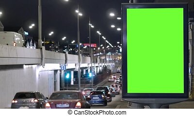 Billboard with a green screen, located on a busy street. Cars move in the evening.