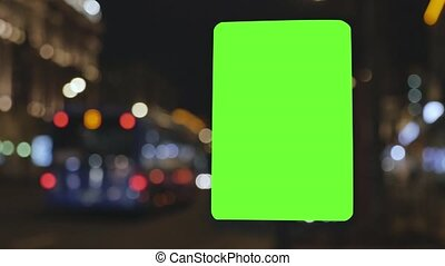 Billboard with a green screen, located on a busy street. Cars move in the evening. The background is out of focus