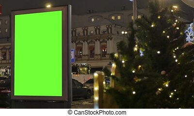 Billboard with a green screen, located on a busy street. The city is decorated for the new year. Cars move in the evening.