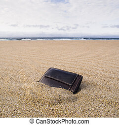Billfold on the beach over the sand
