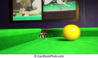 billiard ball rolling into a hole on a pool table