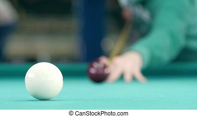 Billiard balls roll on the green table. Slow motion
