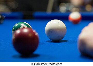Billiard pool in progress, balls are on blue table cloth