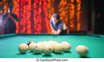 Billiards club. A man aiming and hitting the ball. The game...