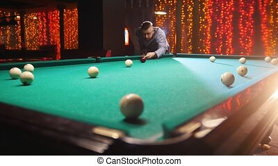 Billiards club. A man in costume aiming and hitting the...