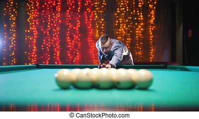 Billiards club. A man in glasses aiming and hitting the...