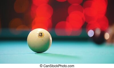 Billiards club. A man playing billiards. A cue hitting the ball with 13 number. Mid shot