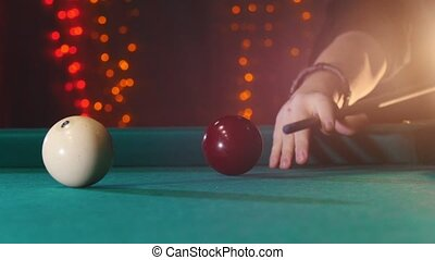 Billiards club. A person playing billiards. A cue hitting the ball. Mid shot