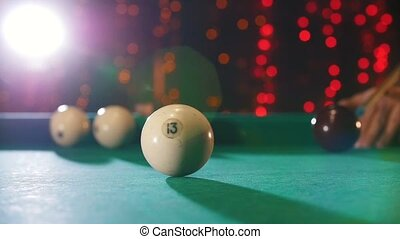 Billiards club. A person playing billiards. A cue hitting the ball with 13 number. The balls clashing. Mid shot