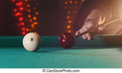Billiards club. A person playing billiards. A cue hitting the ball with number eight. Mid shot
