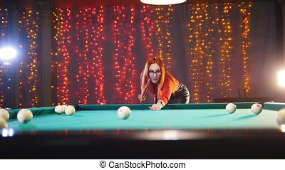 Billiards club. Concentrated ginger woman in glasses aiming...