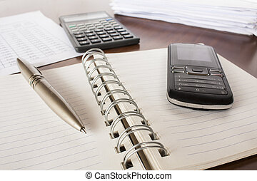 bills ,pen .cell phone, notebook and calculator, accounting