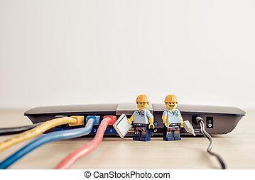 Billund, Denmark - July 15, 2021: Technicians connecting network cable. Illustrative editorial