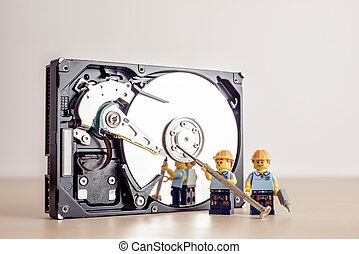 Billund, Denmark - July 15, 2021: Technicians fixing HDD drive. Illustrative editorial