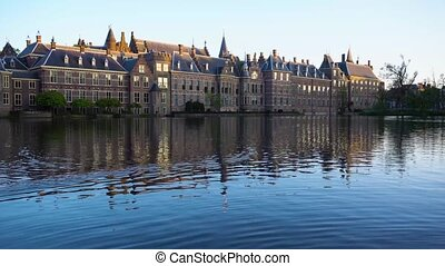 Binnenhof - Dutch Parliament with reflections in pond water, The Hague at spring with tulips flowers, Holland