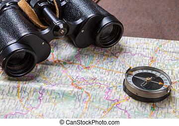 Binoculars and compass on map.