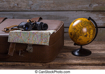 Binoculars and map on suitcase.