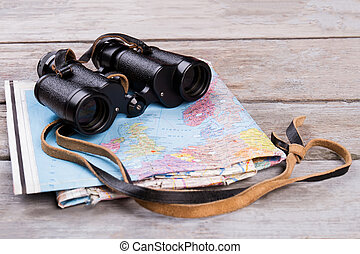 Binoculars and map on wooden table.