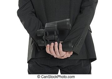 Closeup of a man holding a pair of binoculars behind his back, isolated on white