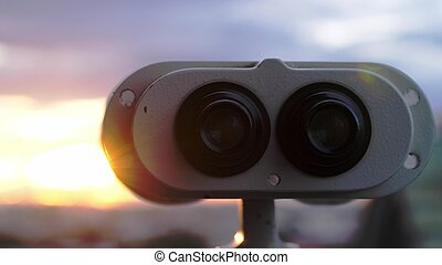 Binoculars lookout at the city during amazing sunset